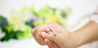 Dziecko trzyma kobietę za rękę