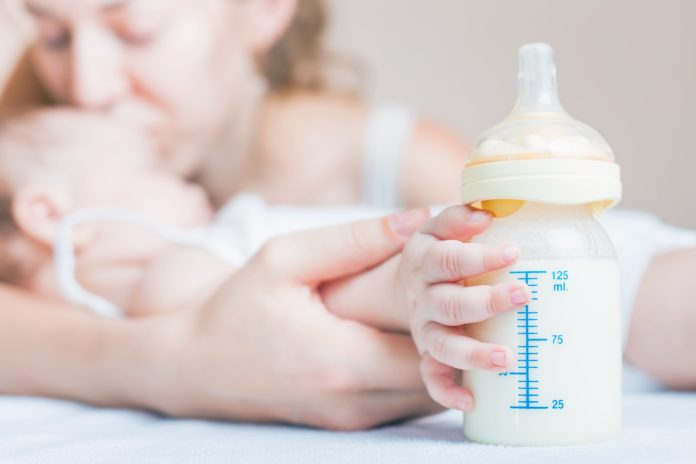 Dziecko trzyma rękę na butelce z mlekiem