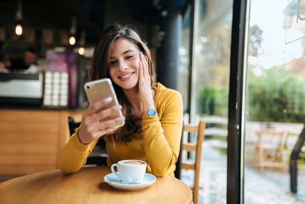 Kobieta w restauracji patrzy w telefon