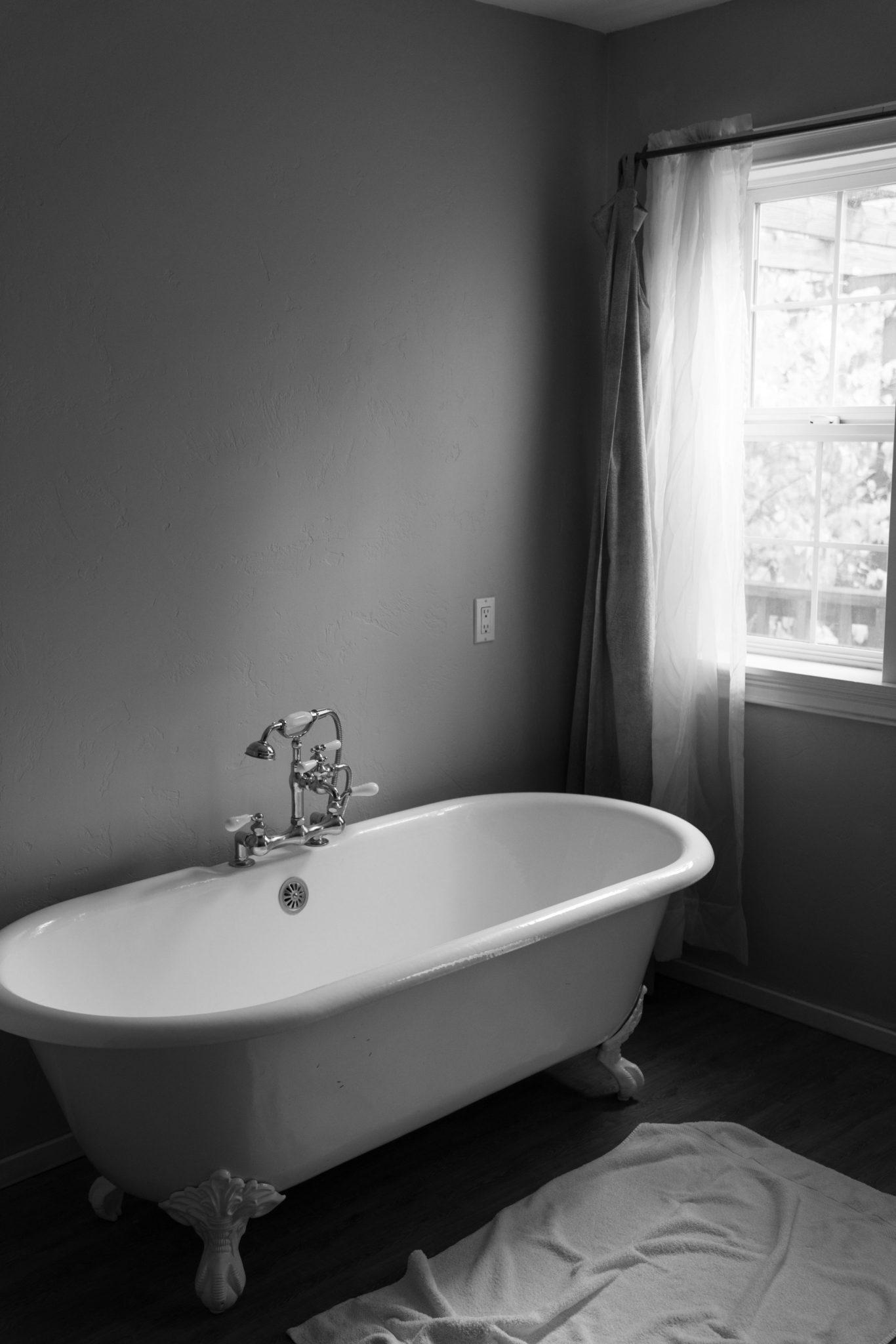 Biała wanna w ciemnoszarej łazience
