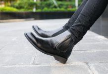 Kobieta siedzi w czarnych botkach na murku