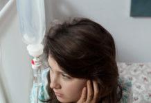 Kobieta siedzi z podłączoną kroplówką