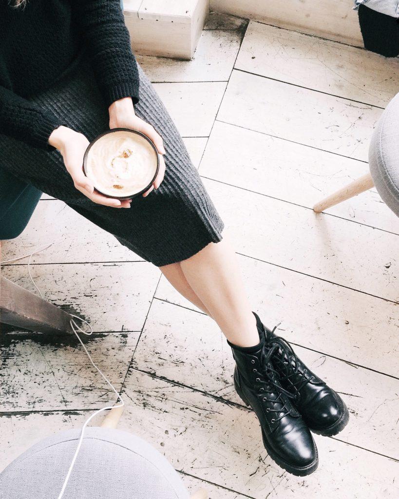 Kobieta w czarnych botkach pije kawę