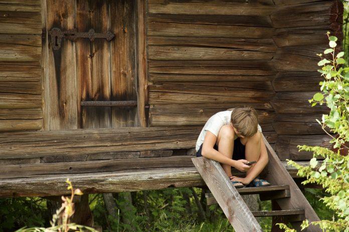 Dziecko w lesie siedzi ze smartfonem
