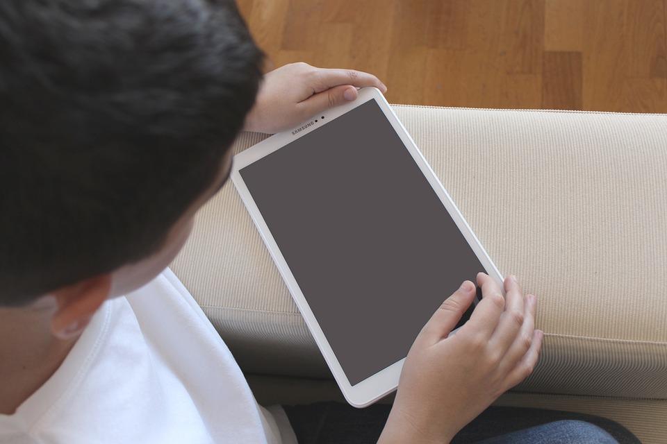 Dziecko z tabletem siedzi w domu
