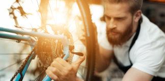 mężczyzna naprawiający rower