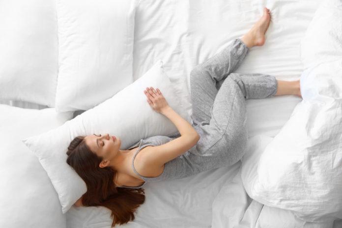 Kobieta śpiąca na boku na łóżku na poduszce