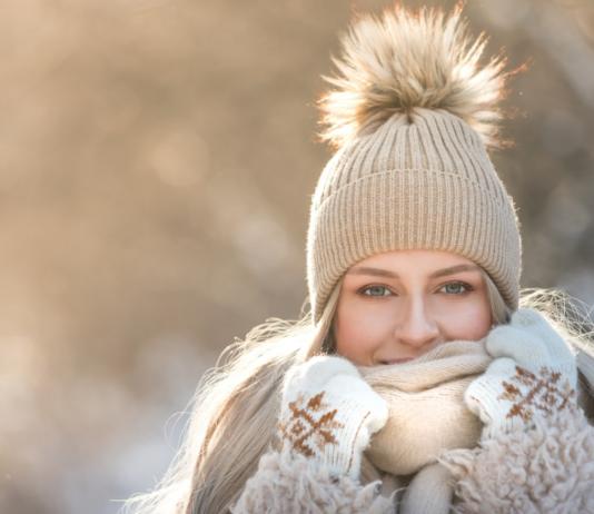Kobieta w beżowym stroju i czapce z pomponem na zimowym tle