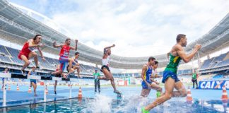 Mężczyźni biegnący przez przeszkodę wodną