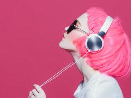 dziewczyna w różowej peruce na różowym tle słuchająca muzyki na słuchawkach nausznych