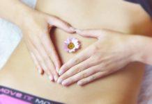 Kobiecy brzuch z kwiatkiem w pępku