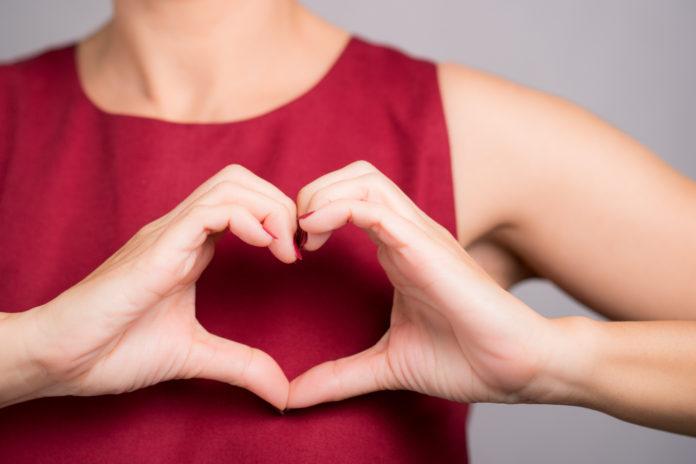 kobieta z rękami trzymanymi w kształcie serca