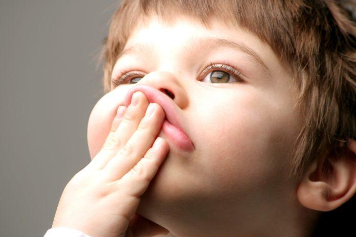 dziecko z rączką na buzi