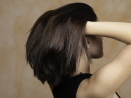 Szatynka delikatnie unosząca półdługie włosy
