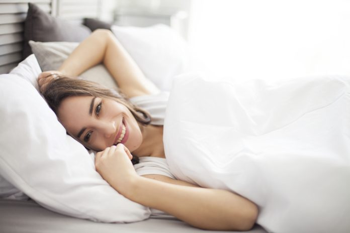 kobieta przeciągająca się o poranku w łóżku