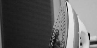 czarno białe zdjęcie żelazko obok uprasowanego ubrania