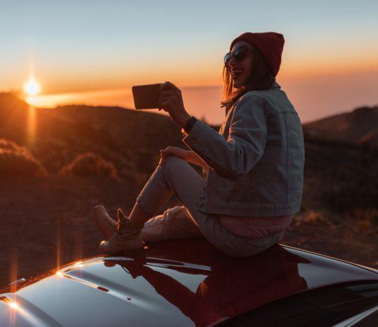 dziewczyna na dachu samochodu filmująca krajobrazy