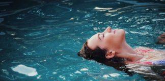 kobieta w wodzie pływająca na plecach