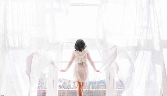młoda kobieta stojąca w oknie przy rozsuniętych firankach