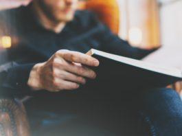 mężczyzna czytający książkę o rozwoju osobistym