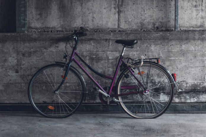 rower z bagażnikiem stojący przy betonowej ścianie