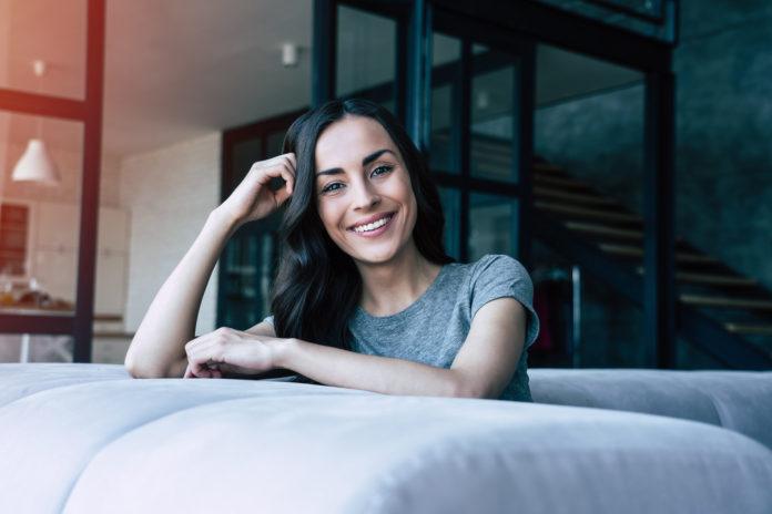 uśmiechnięta szatynka siedząca na kanapie
