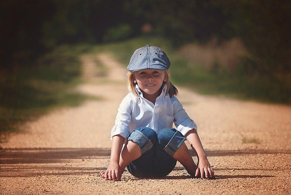 chłopiec w jeansowym kaszkiecie na drodze