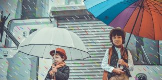 dwaj chłopcy w czasie deszczu pod parasolkami