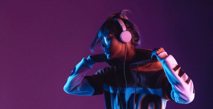 dziewczyna w różowych słuchawkach na uszach słuchająca muzyki