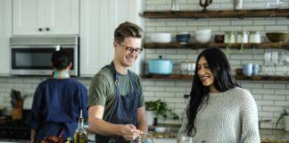 młodzi ludzie wspólnie gotują w domu