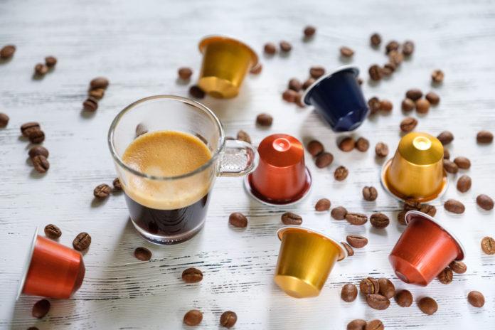 szklanka espresso obok kapsułek kawy i ziaren kawy