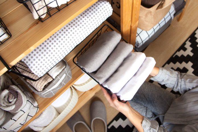 kobieta układająca ręczniki w łazience w pojemnikach