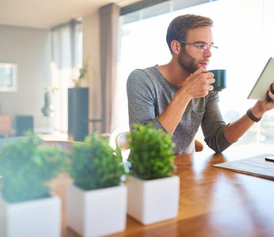 młody mężczyzna czytający prasę na tablecie przy kawie
