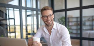 młody przystojny biznessmen przed laptopem z kawą