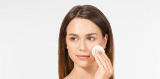 kobieta przecierająca twarz wacikiem kosmetycznym nasączonym płynem micelarnym