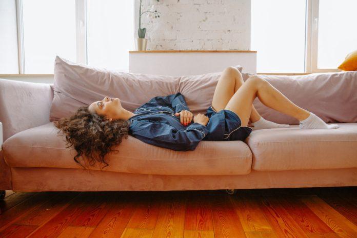 kobieta z bólem brzucha na kanapie