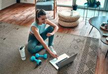 wysportowana dziewczyna z ciężarkami siedząca przed laptopem na dywanie w domu