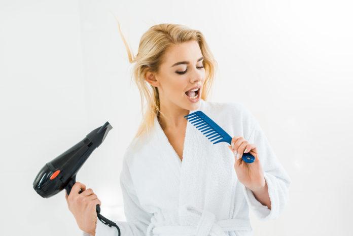 dziewczyna susząca włosy suszarką