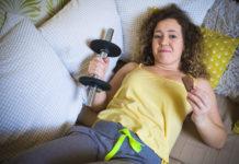 młoda kobieta leżaca na kanapie z ciężarkiem w doni i czekoladką w drugiej