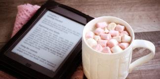 czytnik ebooków ustawiony koło kubka gorącej czekolady z piankami