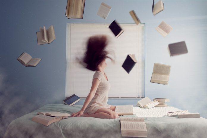 kobieta na łóżku wśród latających książek