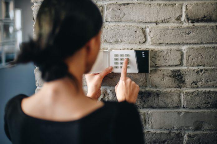 kobieta wpisująca kod do alarmu w domu