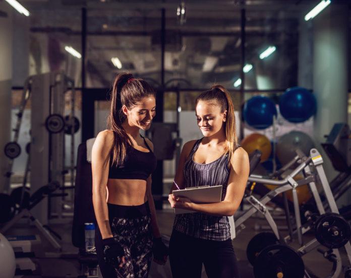 młoda kobieta i trenerka na sali gimnastycznej