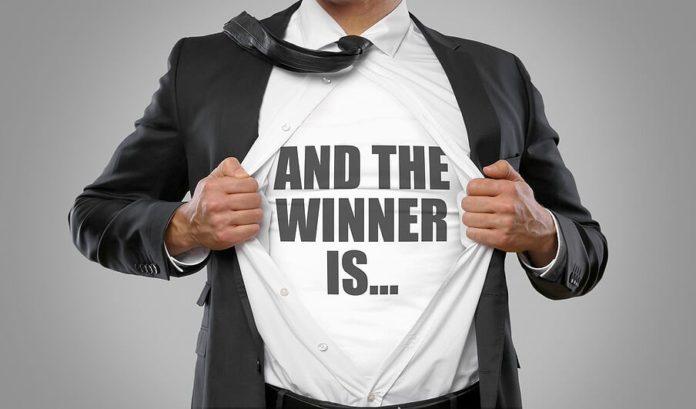 mężczyzna w garniturze z koszulką z napisem and the winner is