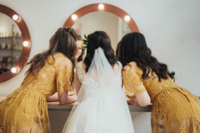przygotowania ślubne, panna młoda i druhny w sukienkach w stylu boho przed lustrem