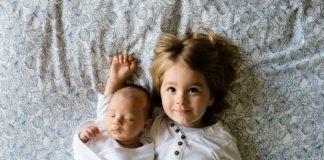 dwoje małych dzieci na łóżku