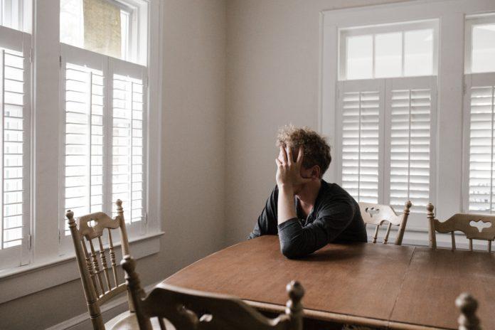 zmęczony mężczyzna siedzący przy stole