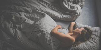 blondynka śpiąca w szarej pościeli