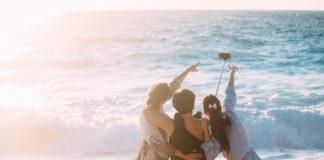 dziewczyny nad morzem robiące selfie przy pomocy selfiesticka