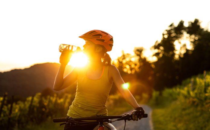 kobieta na rowerze górskim przy zachodzie słońca